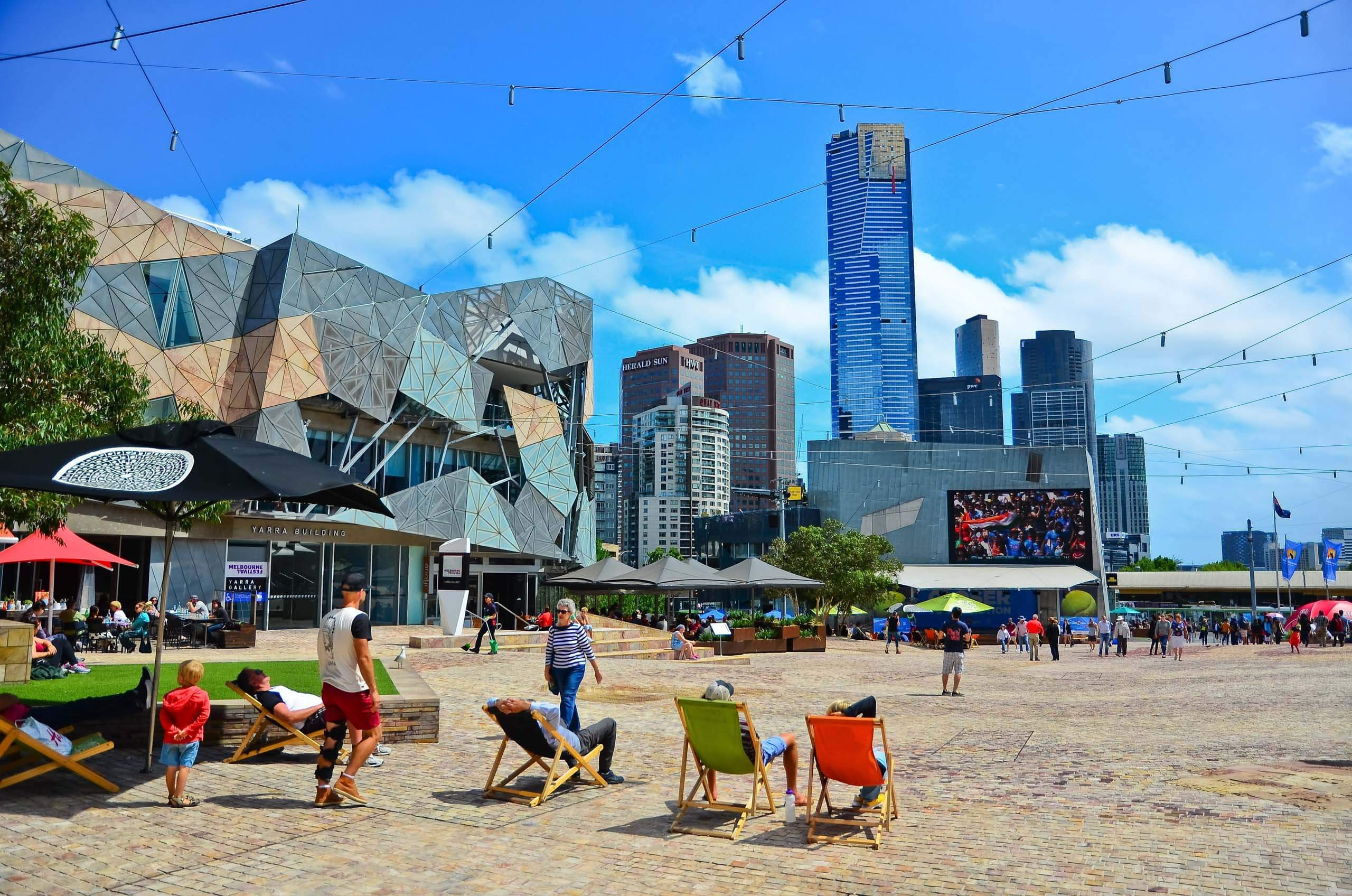 People sitting on deck chairs at Federation Square