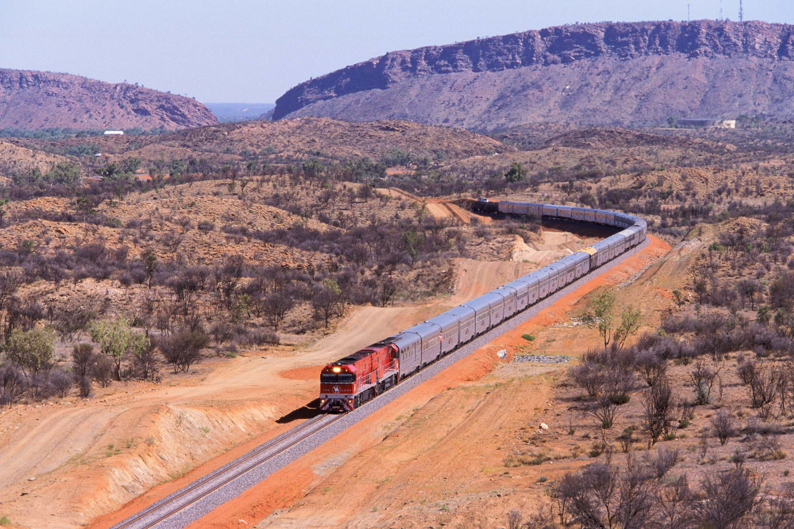 The Ghan near Alice Springs with the MacDonnell Ranges in the background